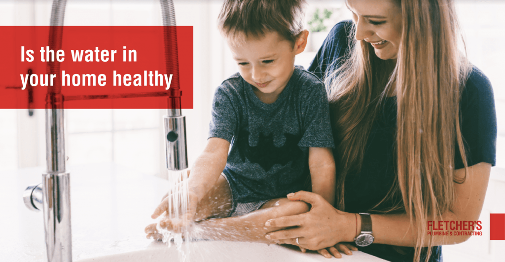 Lady holding child with hand under water faucet