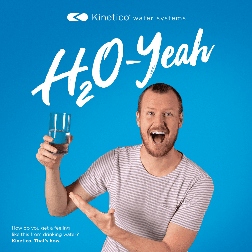 Very happy man holding and pointing to a glass of water