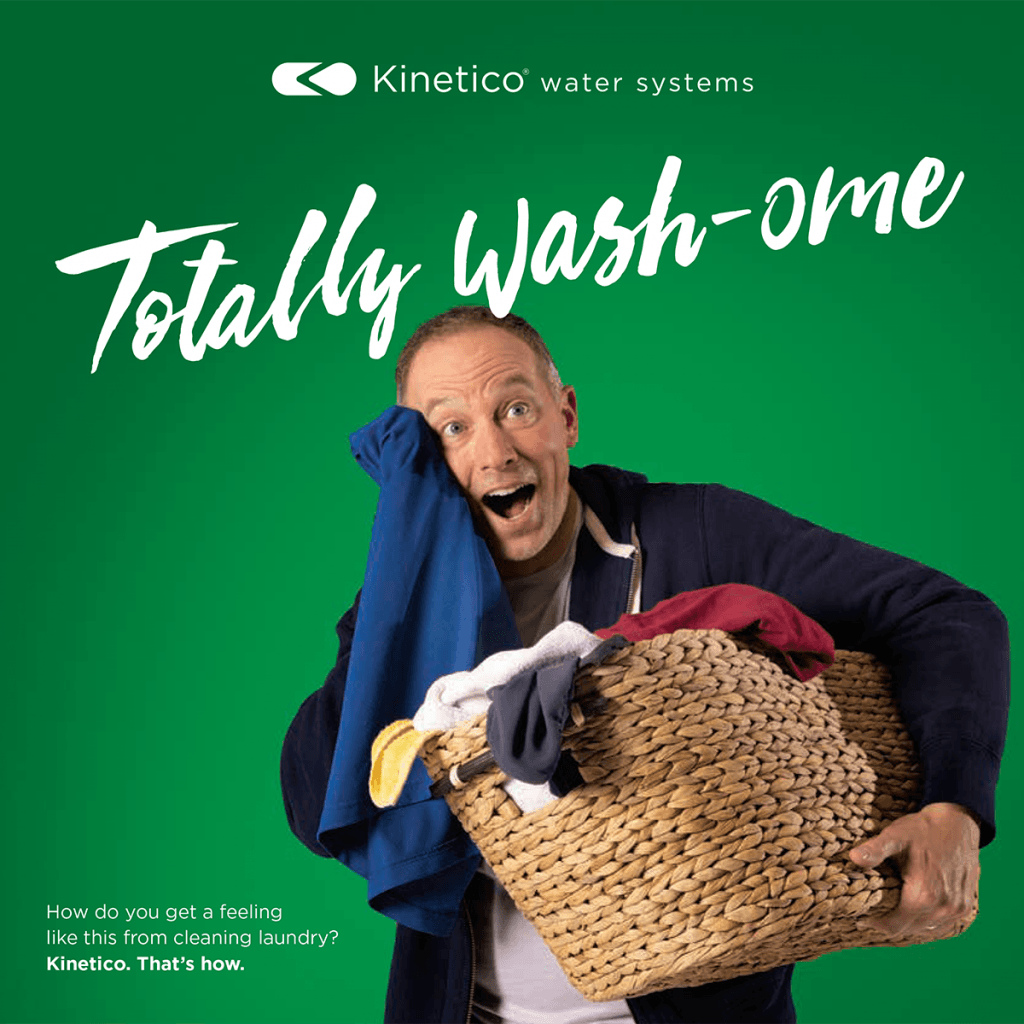 happy man holding laundry basket while wiping soft towel on his face
