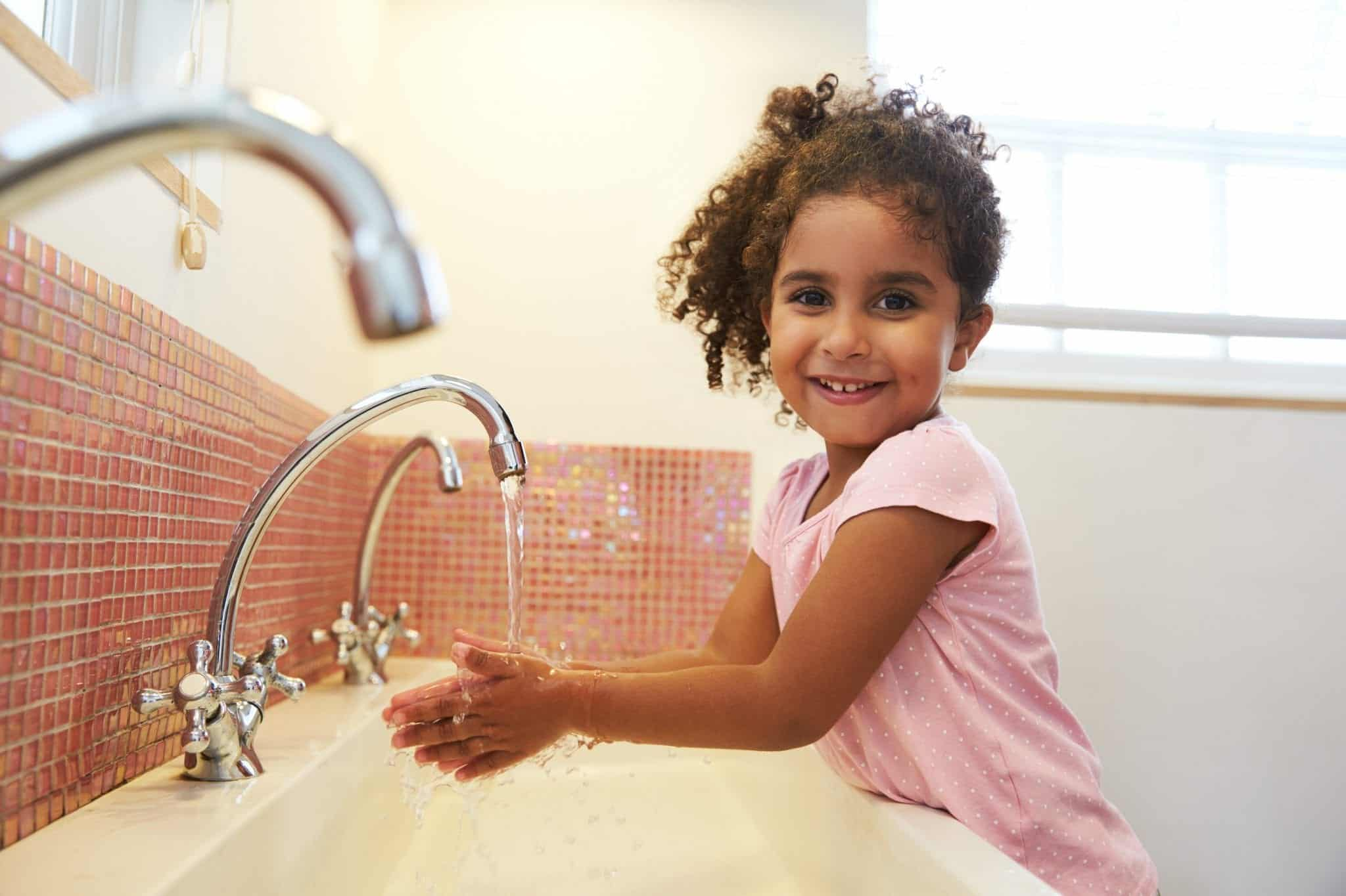 a girl washing her hands and smiling